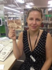 Staff member Natalie holding the postcard, who was only one year old when these postcards were released!